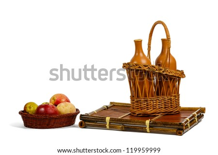 Wattled baskets with apples and ceramic wine bottles on a bamboo support