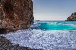 Wave braking on the shore of sa calobra in the valley of the torrent de pareis