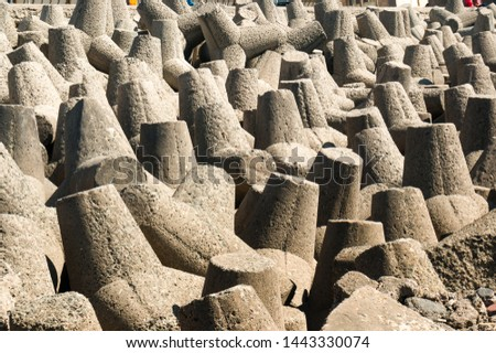 Wave breaker concrete rocks on the side of coastline in Mumbai, Gujarat and other coastlines of india. These shaped rocks are to help reduce the force of waves and ensure they don't damage the coast #1443330074