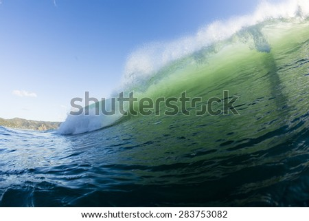 Wave Breaking/ an aqua green wave breaking in evening light on the west coast of New Zealand