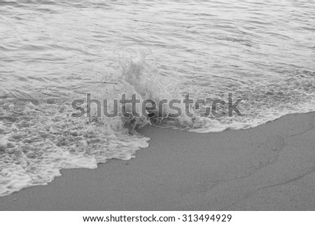 Wave breaking on sand with the focus point on the the breaking wave and a blurred background for use as an advertising backdrop or for use as wallpaper.