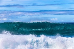 Wave breaking on the western Kona coast of Hawaii's Big Island. Spray and foam in foreground. Pacific ocean, sky with clouds beyond.