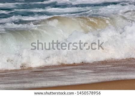 Wave breaks at shoreline Lakes Entrance, Victoria Australia. Gentle rolling wave breaking at shoreline