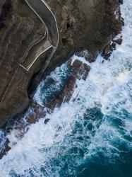 Wave crashing into Bogey Hole rock pool, Newcastle, Australia.