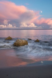 Wave Crashing Over Rocks on Ocean Beach with Pink Sunset Sky