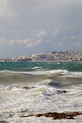Wave crushing and wind blowing over the city of Athens