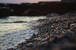 Wave hits the pebble beach
