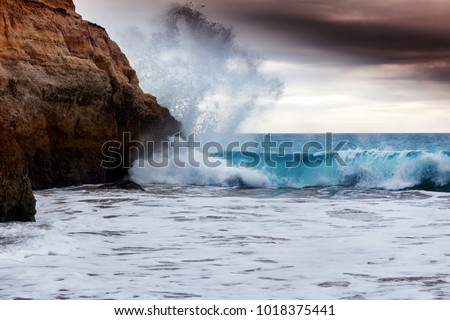 Stock Photo wave is broken against the rocks, beautiful sunset scenery, the Atlantic coast, the Algarve Portugal