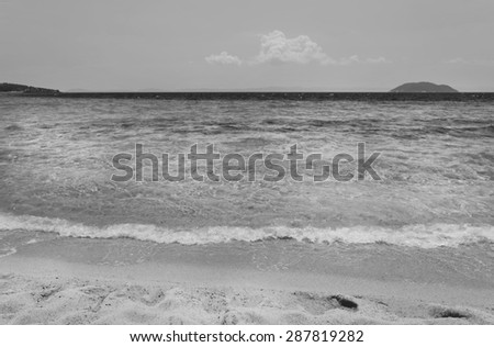 Wave of the sea on the sand beach black and white
