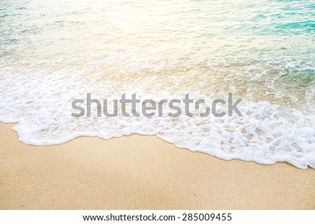 Wave of the sea on the sand beach with sunlight , for background