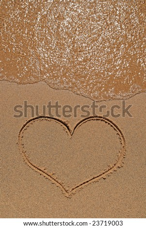 Wave running over the sand beach with heart drawing.
