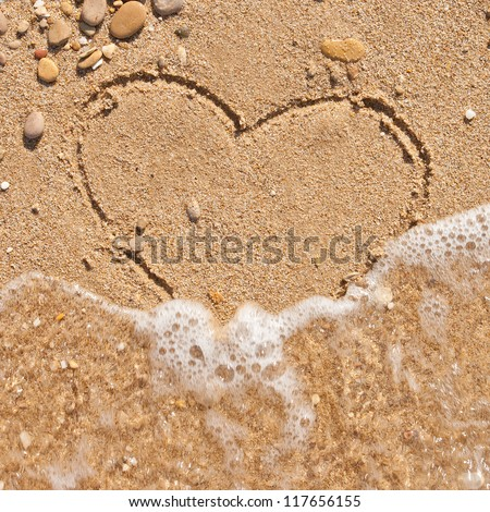 wave washes away the heart on the sand