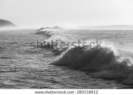 Wave Water Power Black White\ Ocean crashing waters power in black and white along beach coastline,