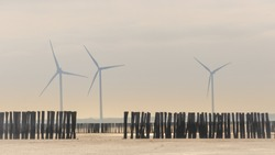 wavebreakers at a dry beach with three windmills in the foggy background at the coast of Zeeland, The Netherlands