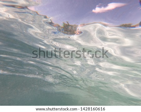 Waves and air bubbles under water. Clear clear water in the pool. Turquoise wave. Sunny summer day. Blue sky