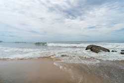 waves and large rocks on the beach. cloudy sky, Arugam Bay, Sri Lanka