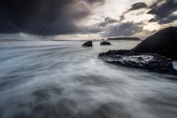 waves approaching the camera with rocks on the right side of the frame and two rocks in the middle ground with a dramatic dark sky while storm is approaching in dark colors in Iceland in the rain