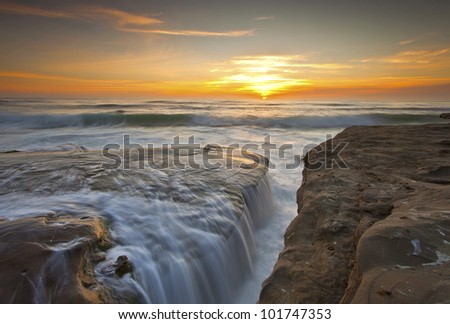 Waves are so high that can create waterfalls on the rock. This was taken at WindnSea beach, La Jolla.