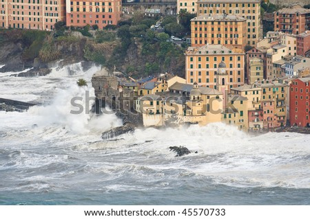Waves break over the church and the castle in Camogli, Italy