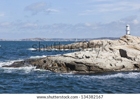Waves breaking at the rocky coast with a lighthouse