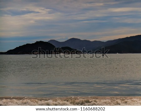 waves breaking gently in a silvery ocean and as background the contours of the island of Florianopolis, sighted of the beach of Pinheirras, under a blue sky with clouds, Palhoca, SC, Brazil #1160688202