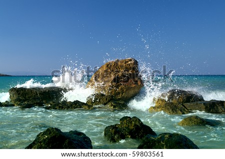 Waves breaking on a stony beach and forming a big spray