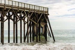 Waves breaking on the poles under the pier of San Simeon, California, USA
