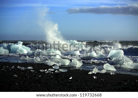 Waves breaking up the icebergs on the beach Iceland