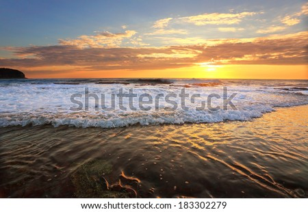 Waves crash and the water flows onto the rock shelf during high tide at sunrise.