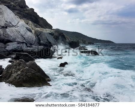 Waves crash on the rocks near a beach, at the Greek island of Skopelos in the Aegean Sea.