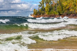 Waves crash on the rocky coast of Lake Superior at Michigan's Pictured Rocks National Lakeshore in autumn. Shot in Michigan's Upper Peninsula not far from Munising.