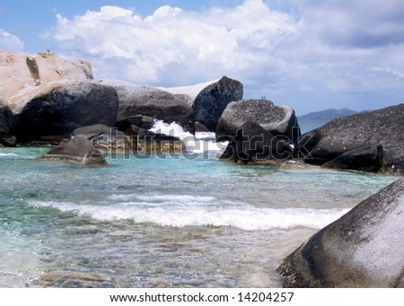 Waves crashing against large granite boulders on the beach of a paradise island.