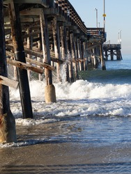 Waves crashing at wooden pier structure background
