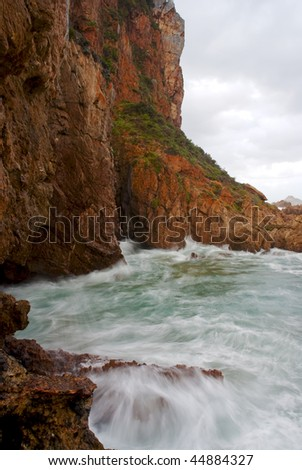 Waves crashing into cliffs protruding into the ocean with stormy clouds above