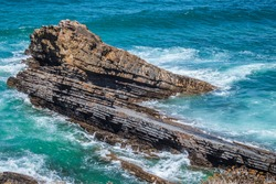 Waves crashing on a fantastic laminated schist rock in the Atlantic Ocean in the Vicentine Coast Natural Park, PORTUGAL