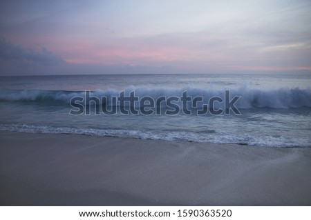 Waves crashing on shore at sunset