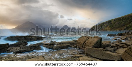 Waves crashing on shoreline with moody dramatic sky at Elgol on the Isle of Skye, Scotland, UK.