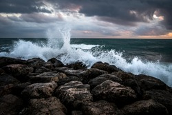 Waves crashing on the black rocks beneath a dark sky