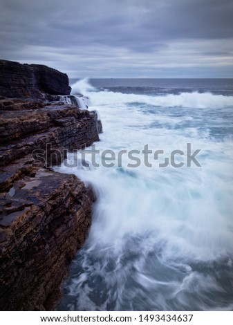 Waves crashing on the brown rocky cliffs of the Irish west coast at dusk (long exposure, portrait) #1493434637