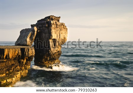 Waves crashing over rock formation cliffs at sunset with beautiful light on rock faces #79310263