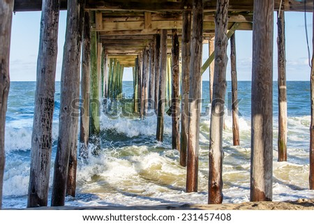 Waves crashing under the fishing pier  #231457408