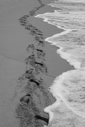 Waves follow the track of human footprints on a beach's sand