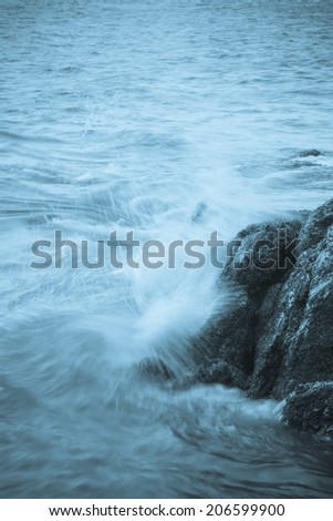 Waves hit rocks with blue tone  #206599900