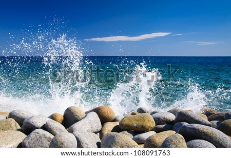 Waves hitting round rocks and splashing #108091763