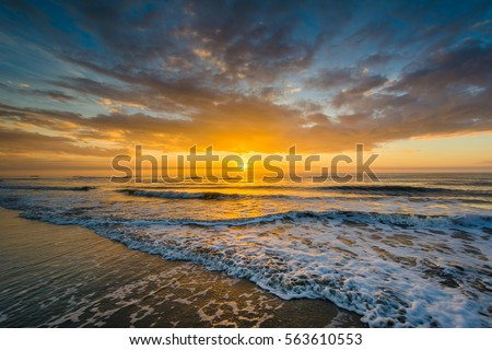 Waves in the Atlantic Ocean and sunrise, in Isle of Palms, South Carolina. #563610553
