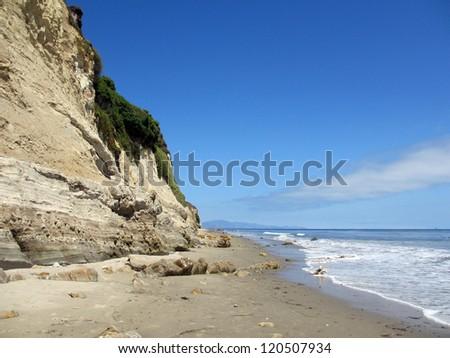 Waves lap on the beach next to tall cliff in Santa Barbara, California. - stock photo