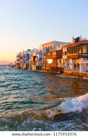 Waves of Aegean Sea and The Little Venice district in Mykonos at sundown, Cyclades, Greece