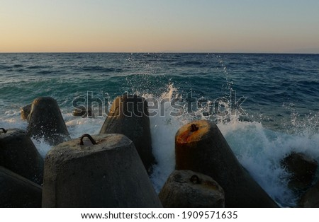 Waves of the Aegean sea hit the breakwaters near the coast of Samos island, Greece ストックフォト ©