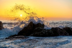 Waves of the Atlantic Ocean crashing against a rock at sunset. Seascape in Portugal, Miramar near Porto.
