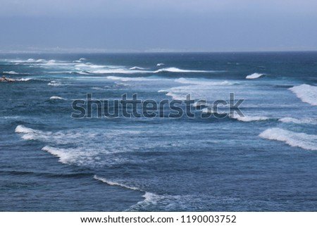 Waves of the Pacific Ocean rolling in while surfers paddle out at Hookipa Beach in Paia, Maui, USA on a hazy day